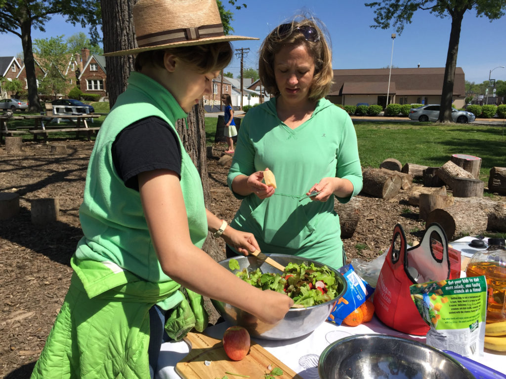 First grader at Mallinckdrodt Academy preparing salad with the help from Amanda Doyle a parent of a 2nd grader at Mallinckrodt.